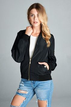 Lightweight bomber jacket in black with gold hardware. It has two front pockets and one pocket on the left arm. Inside lining is orange. Also available in olive.