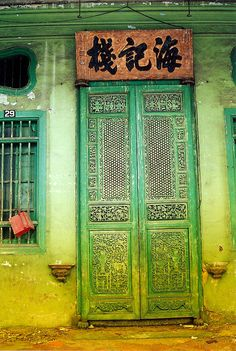 delicately ornate chartreuse screen door topped with a sign bearing logograms painted in heavy black strokes    by Monica Forss, via Flickr