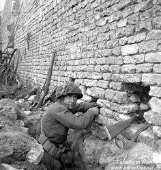 Iinfantryman of 'D' Company, Regina Rifle Regiment, on guard duty in forward post, Normandy, 10 june 1944.