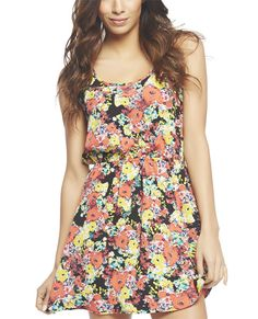 """This tank dress is simply perfect for spring! It features a bright floral printed soft woven body with a double scoop neck, elasticized waist, and a flared skirt.  Model is 5'9"""" and wears a size small      100% Polyester     Hand Wash     Imported"""