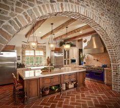 Exquisite kitchen with stone walls and terracotta tile herringbone flooring [Design: Thompson Custom Homes]
