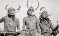 Shoshoni men in feather headdresses blow eagle bone whistles as part of a Sun Dance in Fort Washakie (Fremont County), Wyoming.