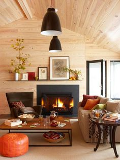 Use natural textures to create a warm, fall-inspired mood. With pine-clad walls, expansive windows, and fiery colors, this living room takes on indoor-outdoor style. Hints of black in the fireplace surround and overhead light fixtures balance the room's outdoor feel with clean, modern design.