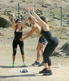 Never a break from working out: Exercising with her trainer and sister Khloe while on the ...