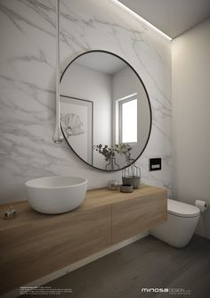 This powder room packs the WOW factor with a huge circular mirror and marble wall covering.