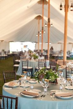 Sperry tent with fruitwood chivari chairs.  Table numbers on small framed chalkboards.
