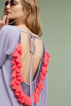 The open back on this sunshine-ready cover-up is embellished with handmade tassels and a delicate tie-back.