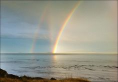"""A triple rainbow. Double rainbows are fairly common, but the vertical rainbow that connects from the base of the primary rainbow to the second rainbow is called a """"reflection rainbow"""" -- caused simply by sunlight reflecting off the body of water and, in essence, making a second sun to create a new rainbow."""