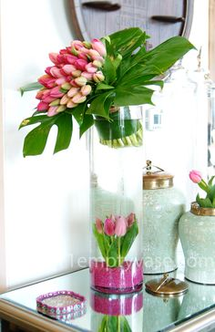 Dutch tulips arranged in a french bouquet style, made to fit in a tall glass cylinder vase with tulips and gravel accenting the base.