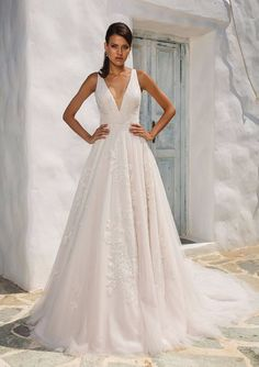 Vintage inspired deep V-neckline with hand placed beaded lace. A pleated waistband, hand beaded lace appliques that float across the skirt of this English net, and finished covered buttons adorn the gown.