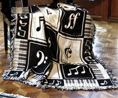 This afghan throw blanket features keyboard keys, notes, and staff symbols on a classic black and white.