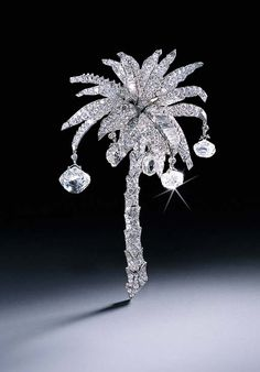 THE CARTIER PALM TREE DIAMOND CLIP BROOCH  Set with circular and baguette-cut diamond leaves with briolette-cut diamond coconuts to the pavé-set articulated trunk, 1939