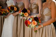 The bridesmaids in Laura's wedding also carried clutch bouquets with similar flowers. Their bouquets included  bi color roses, purple aster, orange garden roses, craspedia, red and orange dahilas, green hydrangea, green cymbidium orchids, Queen Anne's lace, green hypericum berries, dusty miller, gomphrena, and mango calla lilies. The colors blended beautifully against their champagne colored gowns | by Dorothy McDaniel's Flower Market; Spindle Photography