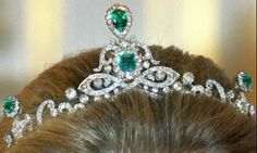 A good frontal view of the emerald tiara, showing the base rowof diamonds rising to crossover and form a bow-shape, on which rests the central emerald and diamond motifs.