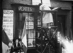 English suffragette Estelle Sylvia Pankhurst (1882-1960) stands on a platform to paint the front of the Women's Social Defence League premises in Bow Road, East London.