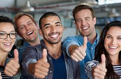 Positive group of creative professionals smiling and showing thumbs-up signs - stock photo #1200195