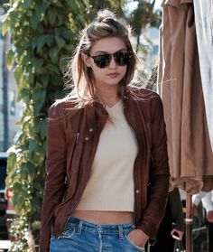 Gigi looks so stylish in a cropped sweater, moto jacket, and jeans.