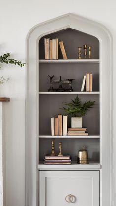 Beautiful styled bookshelf with darker grey behind shelves