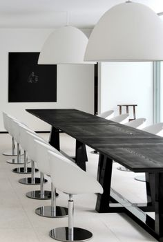 A black almost Asian style table is accompanied by modern white pedestal chairs. Simple but very chic.