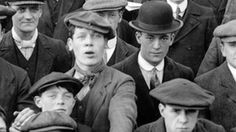 Flat caps as worn by men at a football match in 1913