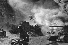 Soviet soldiers walk and drive past a burning T-34 medium tank during the Battle of Kursk, Russia, July 1943. Although the conflict between the Soviet and German forces barely lasted two months it is considered the largest armoured engagement in history. (Photo by Hulton Archive/Getty Images)