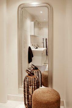 UTUNYTTER PLASSEN: At speil virker romforstørrende er dette interiøret et godt eksempel på. Når døren til badet står åpent, speiler badet seg i gangen og skaper en spennende effelt i den vindusløse lille gangen. Speil fra Balzac Interiør. Kurvpuff og lanterne fra Christian