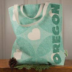 Heart Oregon Fir Tote   Large – Little Bay Root. Dusted with fir needles and peppered with hearts, this heavy-weight canvas market tote has quickly become a customer favorite. This isn't a cheap, lightweight bag, this one sturdy enough to carry a couple of gallons of milk, if you're into that sort of thing. Seafoam and evergreen ink.