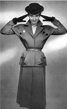 1951 Model in belted grey wool suit, jacket has interesting buttoned pockets, by Nina Ricci,