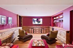 Au sous-sol du chalet, une salle home-cinema en rouge carmin, fauteuils Lago, coffres cuir et métal