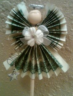 Cash Money Gift Ideas: We are in love with this DIY Christmas Dollar Angel that we found on Pinterest. Unfortunately, there's no credit given so we don't know where it came from. It's made with 3 one dollar bills. Each wing is a dollar and the gown is one dollar. The flower and bow are glued to a button. The button is attached to the wire that holds the dollars together as well has the bead head and halo. The halo is a decorative wedding band.