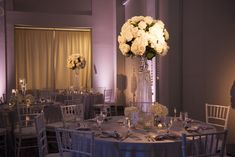 Wedding Reception Table Decor with Tall, Crystal Centerpieces with White Flowers and Crystals and White Chiavari Chairs | Pinspotting and Pink Uplighting by Tampa Wedding Lighting Nature Coast Entertainment