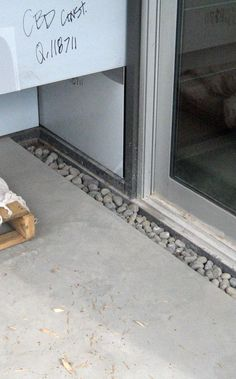 Trench-drain-between-sliding-door-and-concrete-slab-0-filled-with-river-rock