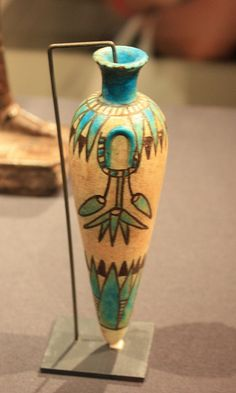 Perfume Vase Egypt, New Kingdom, late Dynasty 18, ca. 1350-1309 BC  Blue and black petals are arranged like a collar around the neck of this white faience vase