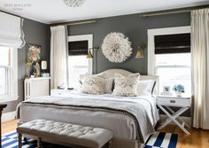 bed with arched headboard, drapes and roman combo, sconces, dark walls and white trim, pom pom quilt