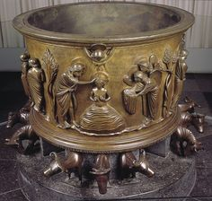 15-29 pg 482. Renir of Huy. BAPTISMAL FONT, NOTRE-DAME-AUX-FONTS. Liège, France. 1107-1118. Bronze, h 60 cm.; diameter 79 cm.  Commissioned by Hellinus, inspired by the basin carried by 12 oxen in Solomon's Temple in Jerusalem. The figures on the font are sturdy but idealized, lifelike, and emotional. There is a strong sense of movement in the piece.
