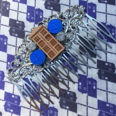This Doctor Who comb is silver in color. It features the a wood engraved Tardis. Rhinestones and a glitter royal blue charm adorn the comb on the
