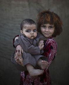 La mirada de los niños afganos refugiados. Khalzarin Zirgul y Zaman. Khalzarin Zirgul, de 6 años, sostiene en brazos a su primo Zaman, de tres meses. La fotografía fue tomada en un suburbio de Islamabad (Pakistán), mientras los pequeños jugaban en la calle con otros niños. (GTRES) Ver más en: http://www.20minutos.es/fotos/actualidad/la-mirada-de-los-ninos-afganos-refugiados-10171/#xtor=AD-15&xts=467263