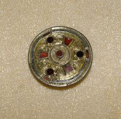 6thC-7thC Silver-gilt keystone garnet disc brooch with 6 garnets around central setting of garnet and white paste.