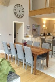 Coastal Retreats The Chimney holiday home. Designed by Richard Grafton Interiors. In the kitchen the soft grey and white colour scheme contrasts perfectly with the natural oak floors and table.