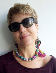 Large beads textile necklace with adjustable loose ends made of digitally printed silk with my own design in a combination of different contrasting colour shades of grey, green, red, magenta and black.