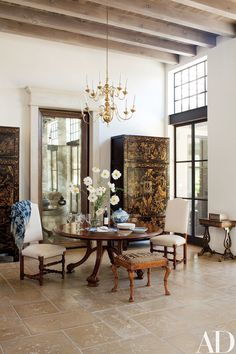 Chinese lacquer cabinets flank a mirrored pocket door that leads from the salon's dining area to the kitchen. The table, set with heirloom Canton china, is by Studio Workshops, and the 19th-century English chairs are upholstered in a Summer Hill linen.