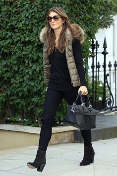 Elizabeth Hurley keeping it simple with a khaki quilted gilet over and all black outfit.