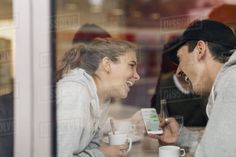 View of happy young couple using smart phone in cafe through glass