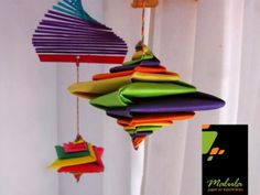 Arco Iris:  La línea Arco Iris de Malula, se caracteriza por los colores decrecientes, semejantes a un Arco Iris, Tirabuzones y Moviles con figuras con origami son protegonistas.     Tirabuzones     Descripción: Tirabuzón arco iris de palitos de madera + Espiral de colores, realizados con  papeles de colores de 15 x15 cm. decorados con canutillos. Línea de 90cm de largo.