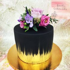 Black and gold cylinder cake fresh flowers