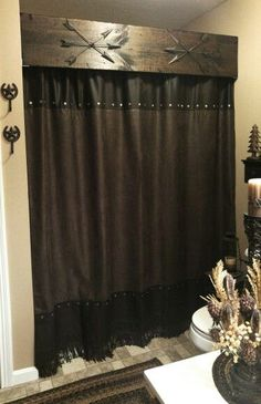 The Blakley House. We love a rustic, western look. The shower curtain has dark brown hues with fringe at the bottom.