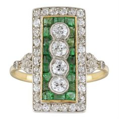 An Edwardian emerald and diamond plaque ring, millegrain rubover-set vertically with four old brilliant-cut diamonds weighing approximately a total of 0.60 carats to the centre of a calibre-cut emerald cluster set in yellow gold within a old brilliant-cut diamond surround all set in white to a yellow gold scrolled mount with diamond-set leaves shoulders and D-section shank, circa 1910.