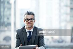 Stock-Foto : Portrait of a businessman outside holding a tablet