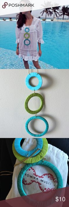 Long multicolored circles tropical style necklace Hand made in Venezuela this statement necklace can make your outfit fabulous. Three smaller to larger circles in blue green and turquoise. Comes in original bag. Jewelry Necklaces