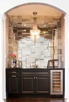 An arched living room alcove is filled with black cabinets fitted with a glass front wine cooler topped with black marble framing a wet bar sink and gooseneck faucet alongside a mosaic tiled mirrored mirrored backsplash illuminated by a fringe chandelier.
